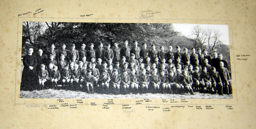 "Class Photo 2 1953.jpg - One of the original photographs taken of the school back in 1953. The picture was supplied by Aiden Bremner.Bert D'Agostino added:-I've had a good laugh at the attached ""original"" photo from 1953.  From memory I always thought there were only 12 of us in the original 1st year class in Oct '53 but I can count 14 in the photo and I can't indentify Gerry Minchella which would make it 15. Also I can't find my brother Gerry who would be in the photo.I can identify the following in the back row from left to right.  ""?"" indicates I'm not absolutely certainJames Robertson?Andrew Robertson?UnknownJack ReganDanny GibbonsJohn Shaw?Eddie StoneDominic MinchellaLudovic ChzrszczBert D'AgostinoLaurence DemarcoFrank StrathiePeter NicollMike Ashley"