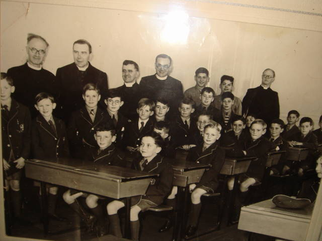 opening day.jpg - Desmond Deighan supplied this photo taken on the openning day of the school in 1953.Desmond was standing directly in front of the then Archbishop Gordon Gray, later to become cardinal. He can remember some of  the names of the other pupils, but you probably know them better than him, as he admits, his grey matter is now very rusty. he was surprised that we did not already have a copy. Have none survived the years? or his he the only hoarder! Back Row:- Bro Hastings, Archbishop Gordon Joseph Grey, Father McLennan, ?, Bertie D'Agostino. Lawrie Demarco, Bro O'Connell Boys standing:- John Shaw, Donald Shaw, Desmond Deighan, David Nelson, Michael Lewis, Freddy Triay,Mike Nagel, ?, ?, Seated :-  John Malone, John Neville, ?, Peter West, Tom Flaherty, Ronnie Rowley,?, ?, Gerry D'Agostino, ?(Thanks for corrections by John Shaw)